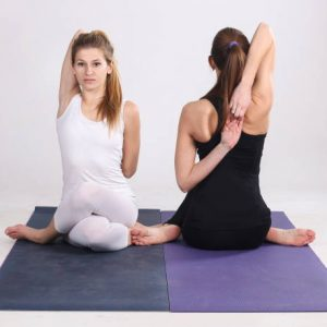 Two young women practicing cow face pose in yoga. Both about 25 years old, Caucasian blonde and brunette.